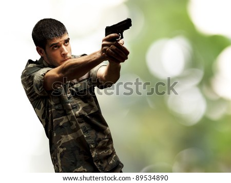 portrait of a young soldier aiming with pistol against a nature background - stock photo