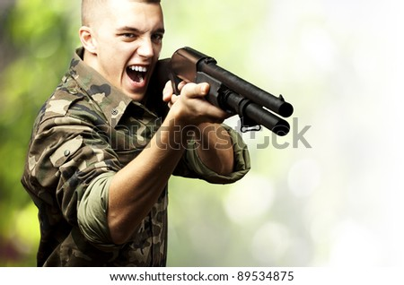 portrait of a young soldier aiming with shotgun against a nature background