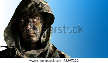 portrait of a young soldier face with hood against a blue background
