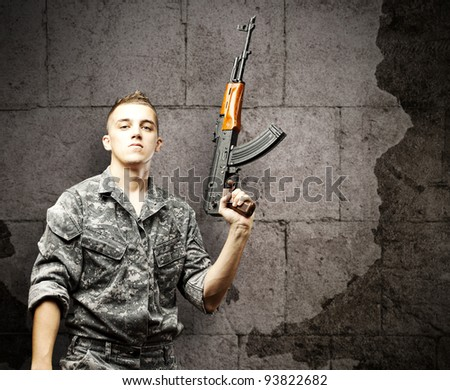 portrait of a young soldier holding a rifle wearing an urban camouflage against a grunge brick wall