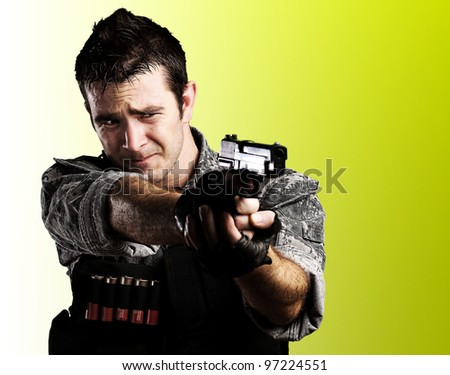 portrait of a young soldier pointing with a gun against a yellow background