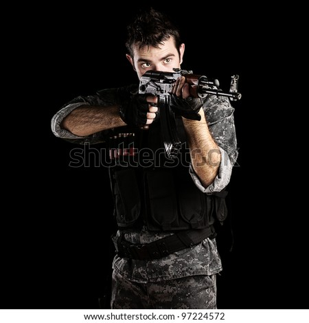 portrait of a young soldier pointing with a rifle against a black background