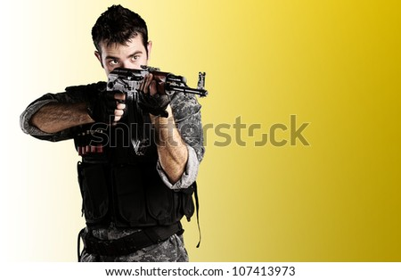 portrait of a young soldier pointing with a rifle against a yellow background