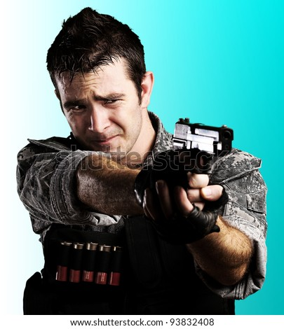 portrait of a young soldier reloading his gun against a blue background