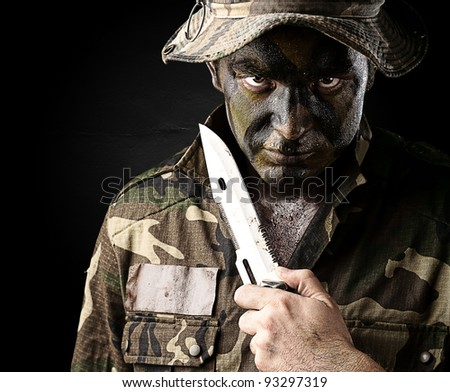 portrait of a young soldier threatening to suicide over a black background