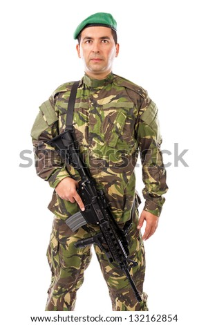 Portrait of a young soldier with a gun against white background - stock photo