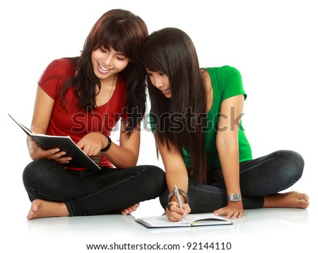 Portrait of a young students smiling while reading a book over white background