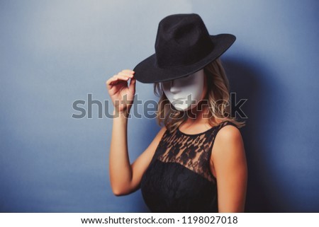 Portrait of a young style girl in black dress and white mask on gray background #1198027018