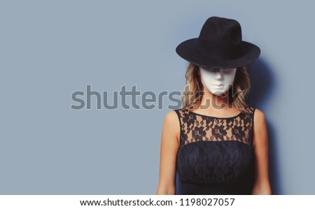 Portrait of a young style girl in black dress and white mask on gray background #1198027057