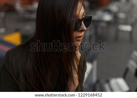 Portrait of a young stylish brunette woman sitting in an outdoor cafe in fashionable black sunglasses. #1229168452