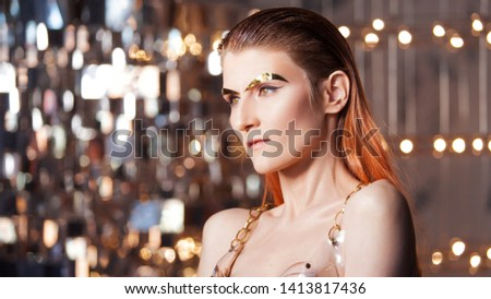 Portrait of a young stylish woman with gold implants on her face. Metallic makeup and eyebrows, futurism concept, fashion of the future. Artificial intelligence and human augmentation