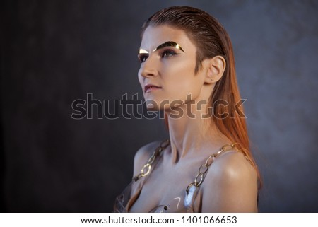 Portrait of a young stylish woman with gold metal eyebrows. Futurism, fashion of the future, concept