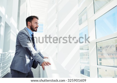 Portrait of a young successful businessman thinking about something while looking in big office building, confident serious men entrepreneur dressed in formal wear enjoying calm after hard work day