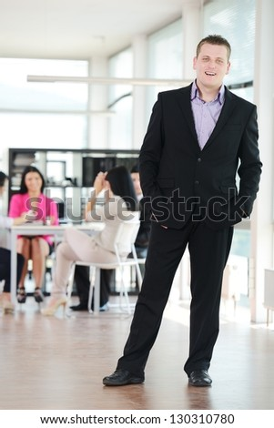 Portrait of a young successful businessman with his team at office