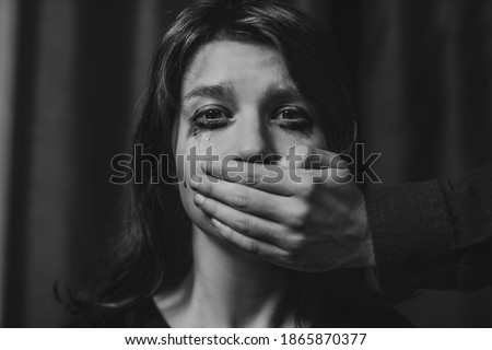 Portrait of a young suffering sad woman with tears in her eyes, a man closes her mouth with his hand. Domestic violence, crying, religion, disagreement, fight, divorce, beating a weaker person, dark. Сток-фото ©