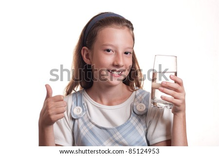 portrait of a young teenager girl drinks water showing thumbs up