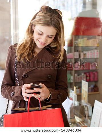 Portrait of a young teenager tourist visiting the city and carrying paper shopping bags while leaning on a fashion store window, using her smartphone device and smiling.