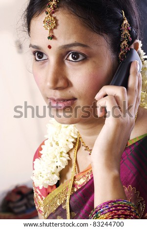 Portrait of a young traditional woman talking on mobile phone