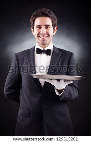 Portrait of a young waiter holding an empty dish on black background