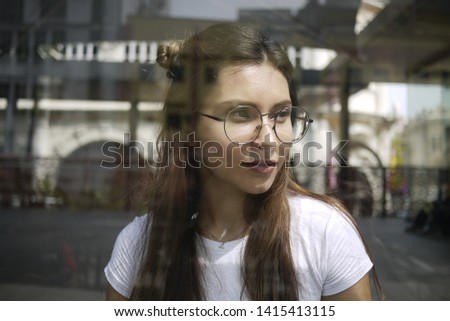 Portrait of a young wearing glasses  through the reflective glass of a window during the day. #1415413115