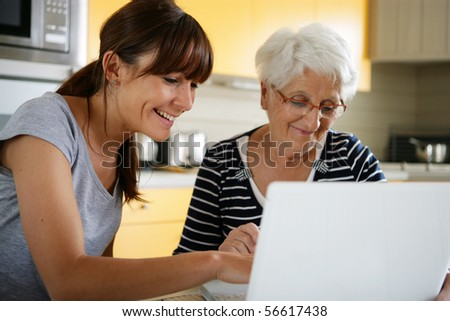 Portrait of a young woman and a senior woman sitting in front of a laptop computer