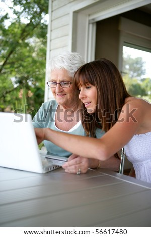 Portrait of a young woman and a senior woman with a credit card in front of a laptop computer - stock photo