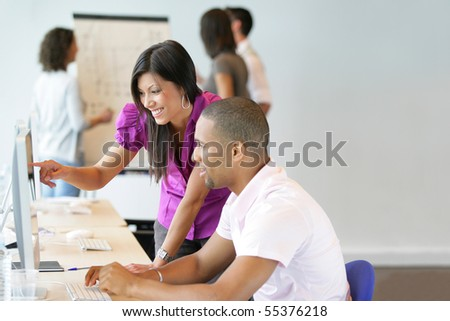 Portrait of a young woman and a young man sitting in front of a desktop computer