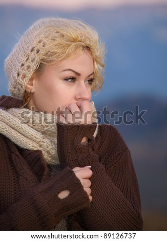 Portrait of a young woman as evening falls in autumn cold.