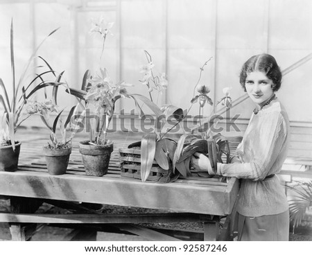 Portrait of a young woman attending  to her orchids