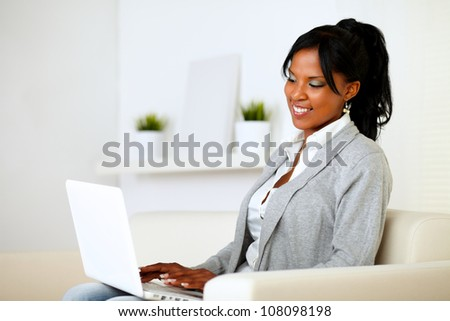 Portrait of a young woman browsing the Internet on laptop while is sitting on sofa at home