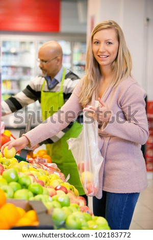 Portrait of a young woman buying fruits with shop assistant in the background