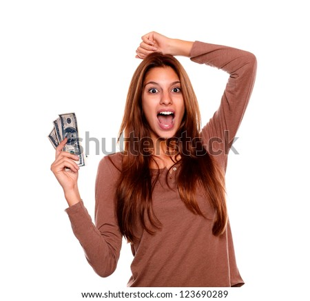 Portrait of a young woman celebrating and holding cash money on brown t-shirt against white background