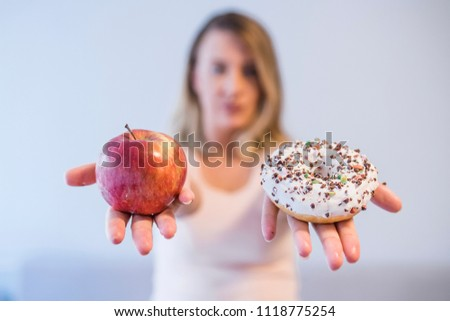Portrait of a young woman choosing between donut and red apple. It's hard to choose healthy food concept, with woman hand holding an red apple and a calorie bomb donut