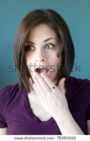 Portrait of a young woman covering her mouth in surprise.