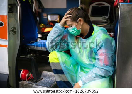 Portrait of a young woman doctor sitting on the ambulance resting exhausted where a first aid intervention during the Covid-19 pandemic, Coronavirus wearing a face mask - Rescue concept Stock photo ©