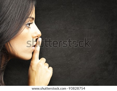 portrait of a young woman doing a silence sign against a grunge background