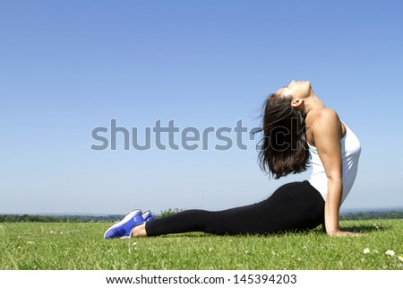 Portrait of a Young woman doing a Yoga Pose and Stretch outdoors
