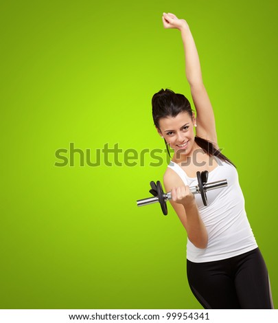 portrait of a young woman doing fitness with weights over a green background