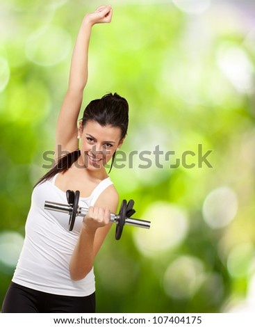 portrait of a young woman doing fitness with weights over a nature background