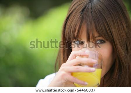 Portrait of a young woman drinking a glass of orange juice