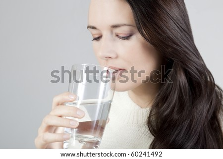 Portrait of a young woman drinking a glass of water. - Shutterstock ID 60241492