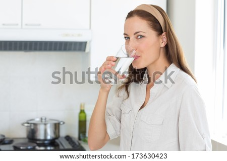 Portrait of a young woman drinking water in the kitchen at home