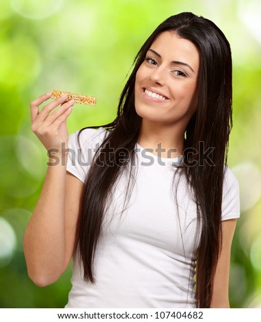 portrait of a young woman eating a cereal bar against a nature background