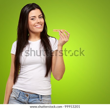 portrait of a young woman eating a cereal bar over a green background