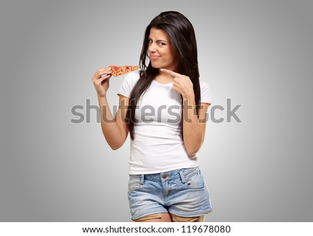 Portrait Of A Young Woman Eating A Piece Of Pizza On A Gray Background