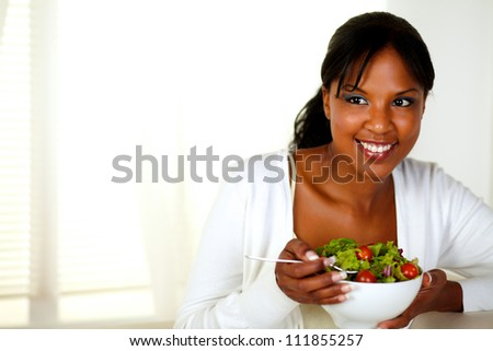 Portrait of a young woman eating healthy salad at home indoor. With copyspace.