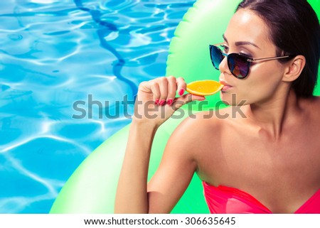 Portrait of a young woman eating orange in swimming pool