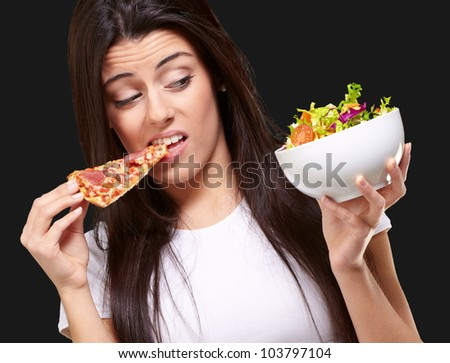 portrait of a young woman eating pizza and looking at a salad over a black background
