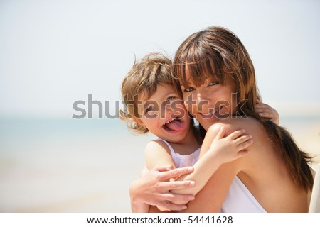 Portrait of a young woman embracing a little girl