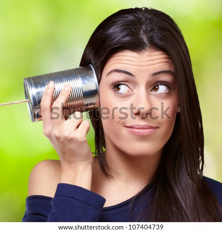 portrait of a young woman hearing through a tin can against a nature background